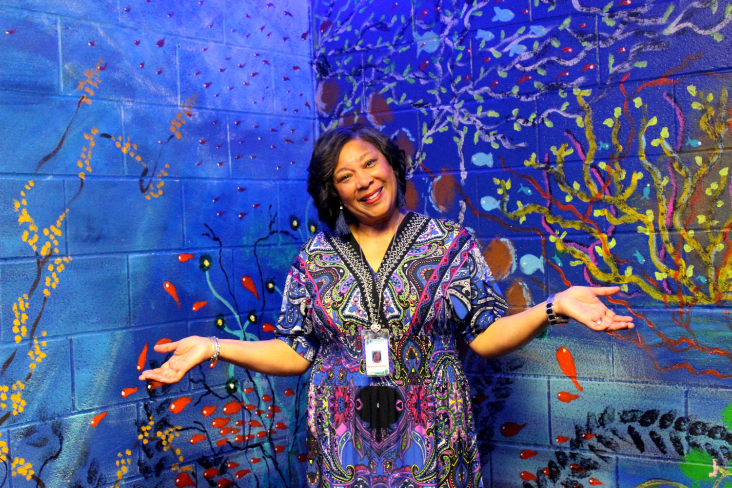 Mrs. Palmer smiles happily in front of the vividly painted walls of the Blue Room.