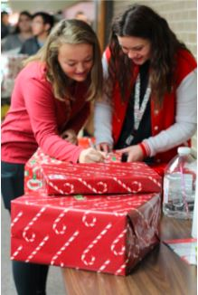 Ally Hunter and Taylor Smith put last minute touches on Winter Wishes gifts.