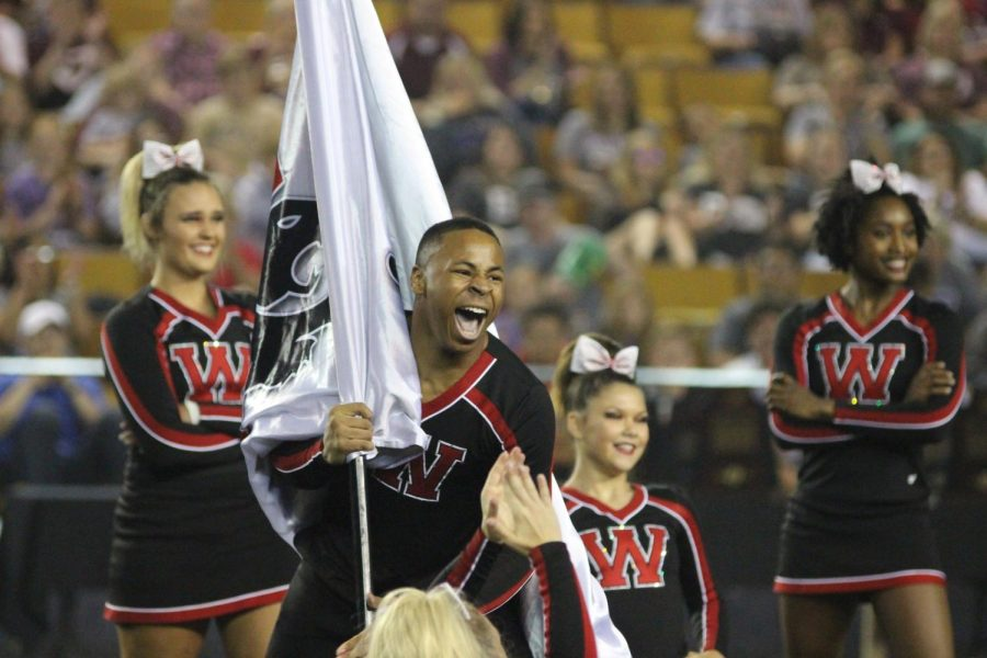 Senior Jordan Fisher shows a face of passion at Cheer State, holding a flag.