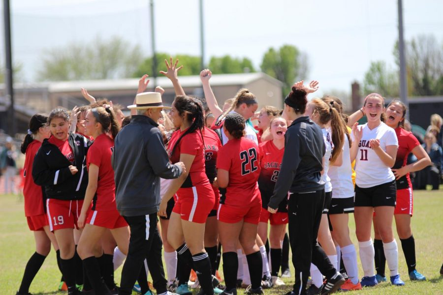 After a match, pitting the girls JV1 against the girls JV2 team, the junior varsity soccer girls embrace in a circle.
