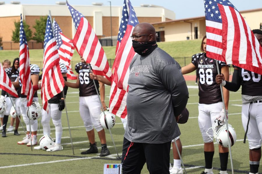 Coach Zo Williams stands along side his players during the moment of silence.