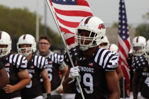 Junior Bralen McCalister, #29 of Varsity Football, runs across the field with an American flag.